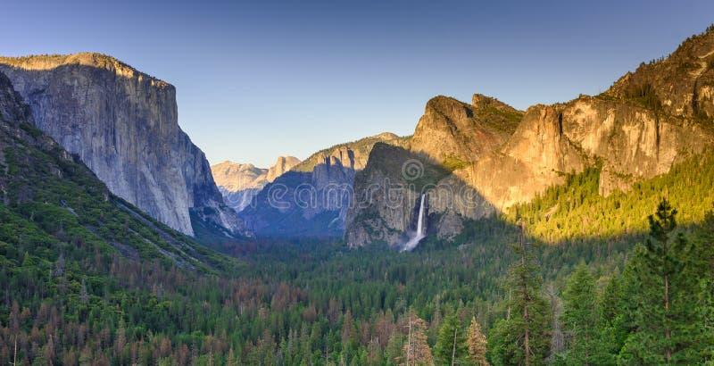 Sikt av den Yosemite dalen från tunnelsiktspunkt på solnedgången - sikt till brud- skyla nedgångar, El Capitan och halvakupolen - royaltyfri fotografi