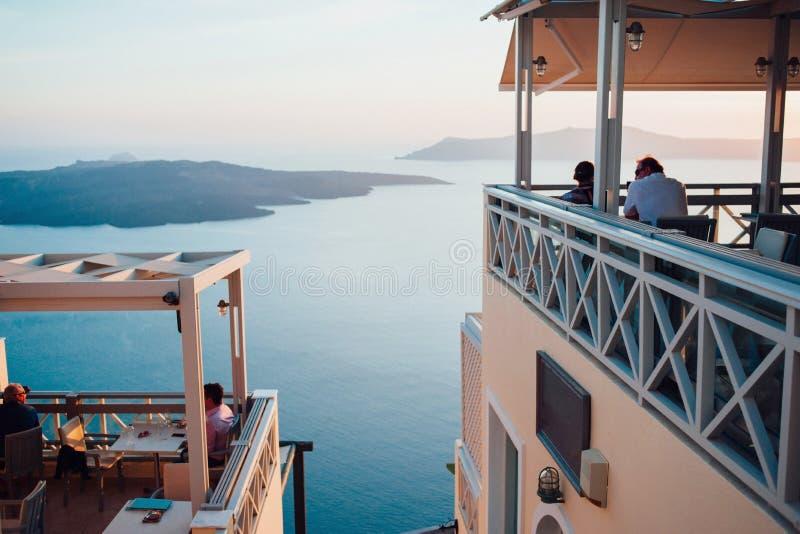 Sikt av denblått solnedgången på ön av Santorini till havet, himlen och öar med folk som tillbaka sitter i ett kafé i royaltyfri fotografi