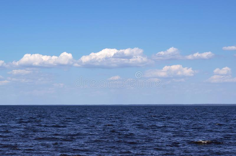 Sikt av det blåa havet med stillsam och ändlös idén den moln, arkivfoton