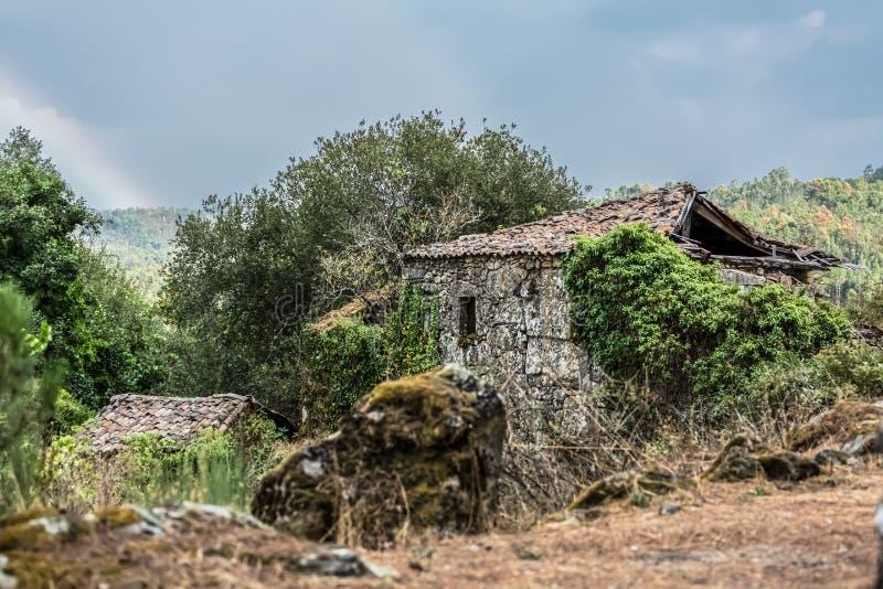 Sikt av det fördärvade stenhuset, med omgeende vegetation royaltyfria bilder