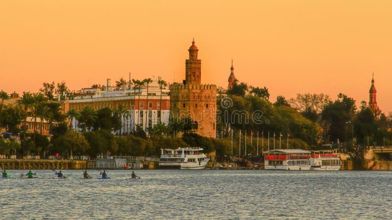 Sikt av det guld- tornet Torre del Oro av Seville, Andalusia, Spanien över floden Guadalquivir på solnedgången royaltyfria bilder