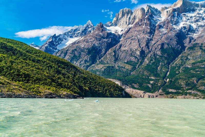 Sikt av det härliga snöberget på kusten av sjögrå färger i den Torres del Paine nationalparken arkivbild