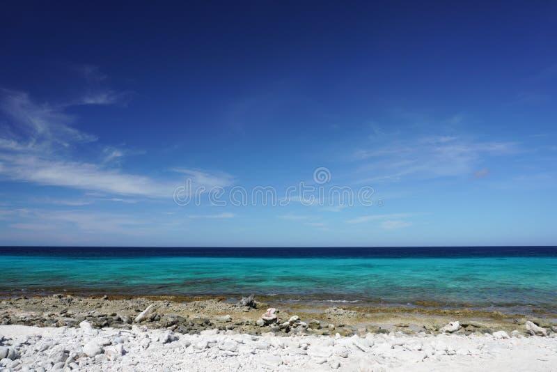 Sikt av det karibiska havet från en stenig strand på ön av Bonaire arkivbild