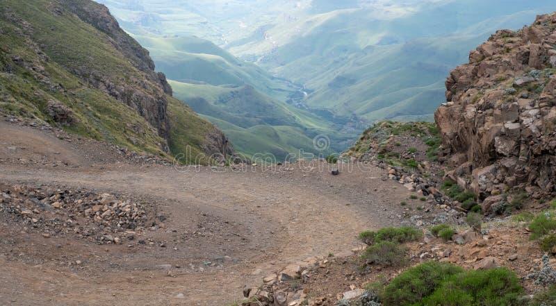 Sikt av det Sani passerandet, spolande lantlig väg för smuts fast bergen som förbinder Sydafrika och Lesotho royaltyfri foto