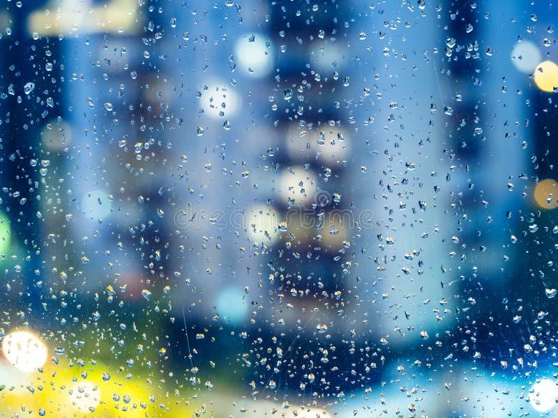 Sikt av det stads- huset till och med regndroppar i afton royaltyfri bild
