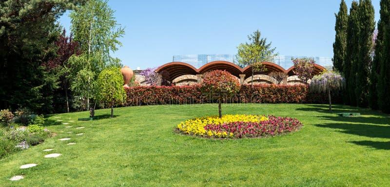 Sikt av en attraktiv trädgård med att blomma blommor, barrträd och välskötta gräsmattor royaltyfri bild