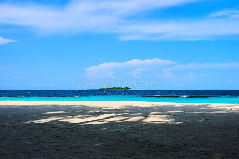 Sikt av en avlägsen liten ö på haven av Maldiverna med moln och blå himmel för frikänd som ses från en strand som läggas med kont royaltyfria bilder