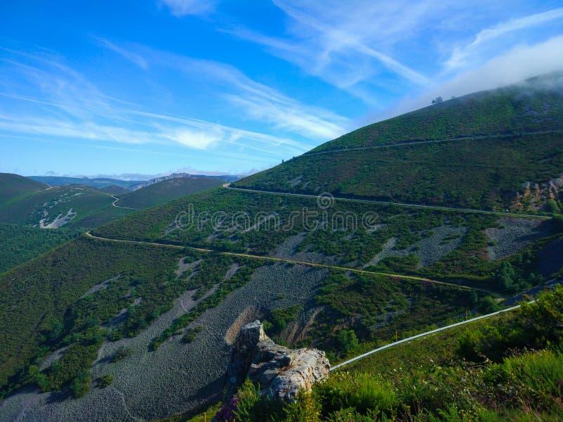 Sikt av en bergväg längs backen Berg för grönt gräs royaltyfri fotografi