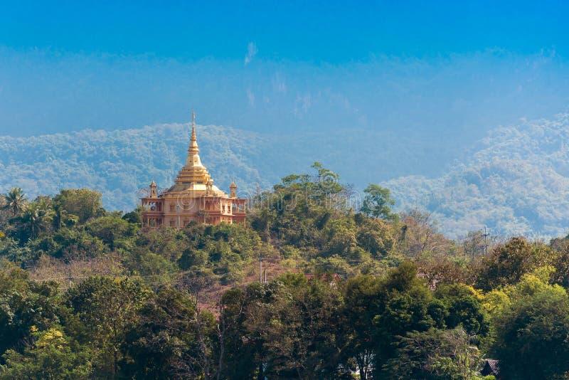 Sikt av en buddistisk tempel i mitt av skogen i Louangphabang, Laos Kopiera utrymme för text royaltyfri foto