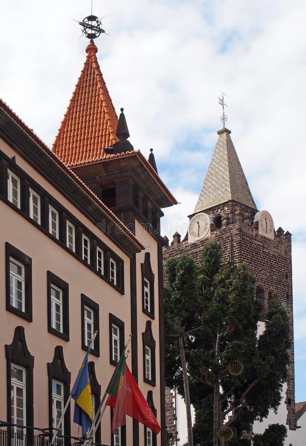 Sikt av en centrumgata i funchal madeira med domkyrkaklockatornet som ?r synligt bak ett tr?d och gamla byggnader med a fotografering för bildbyråer