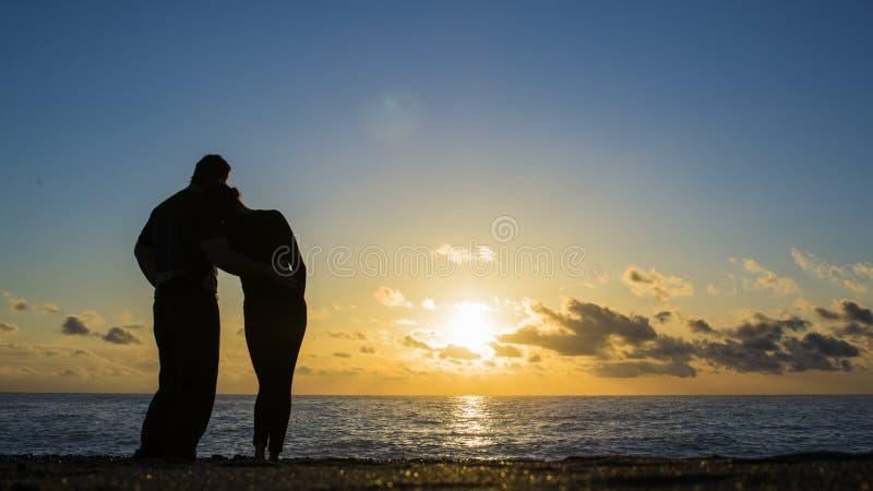 Sikt av en full kropp av en parkontur som tillsammans går på stranden på solnedgången i sommar arkivbilder