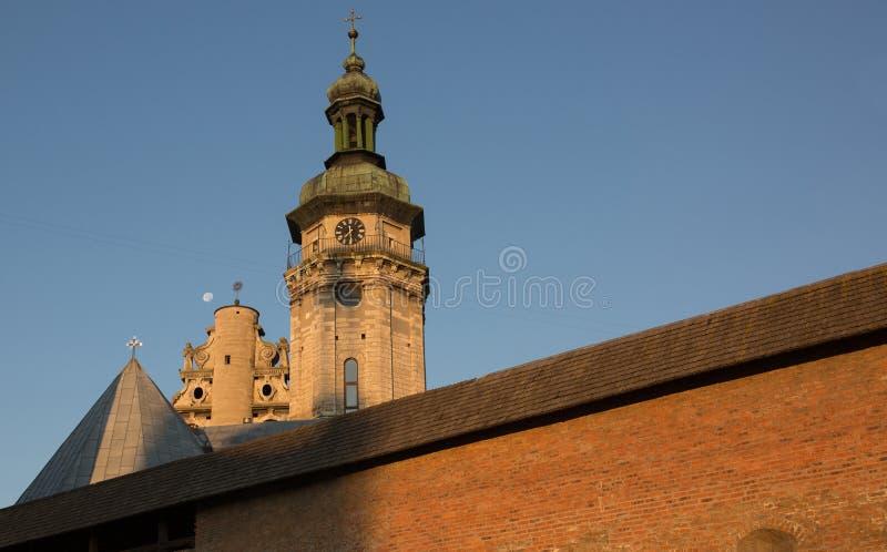Sikt av en gammal kyrka med en kloster i Lviv på soluppgång arkivfoto