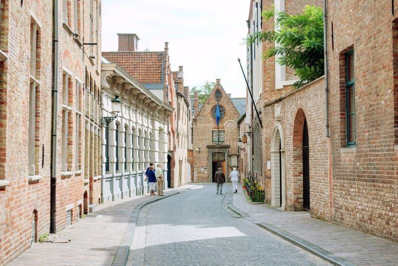 Sikt av en gata i Bruges, Belgien, med historiska byggnader p? en solig sommardag royaltyfri bild