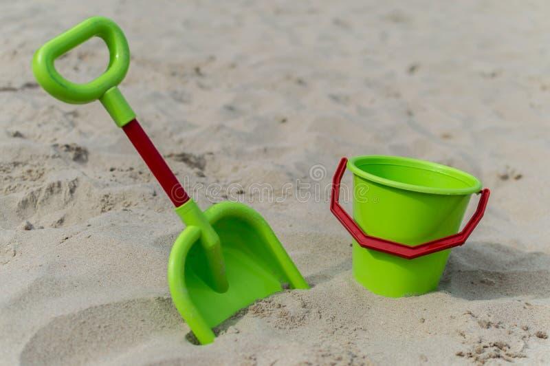 Sikt av en grön hink och skopa på stranden med sand i bakgrunden arkivbilder