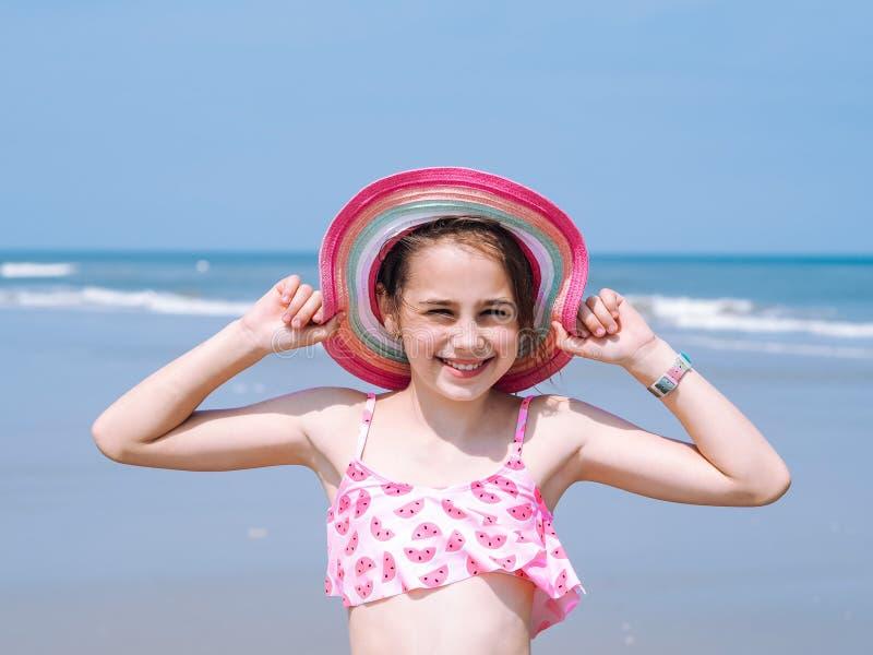 Sikt av en härlig tonårig flicka som bär i färgrik hatt och baddräkten som tycker om sikten på den tropiska stranden arkivfoton