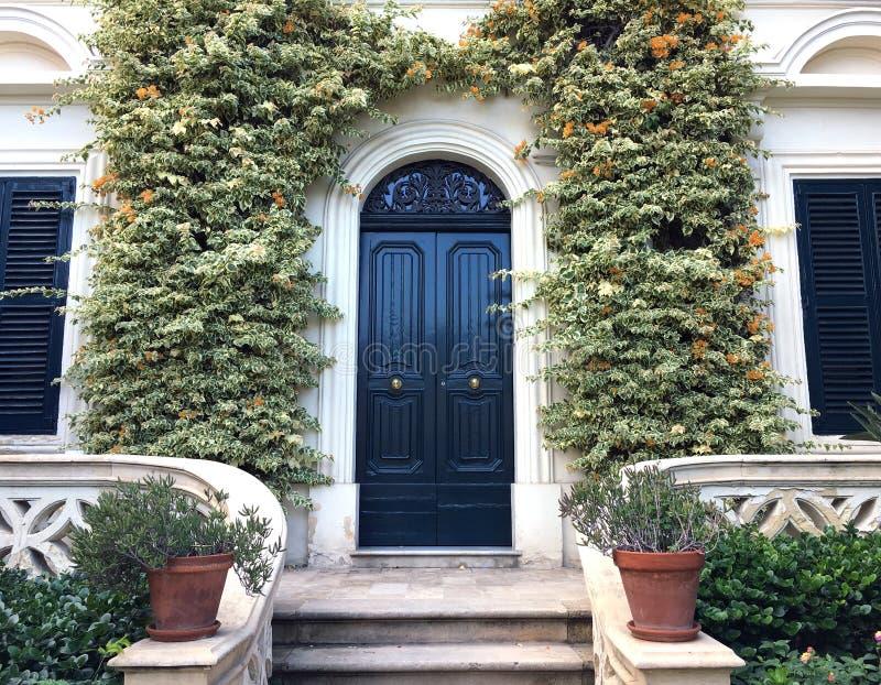 Sikt av en härliga husyttersida och Front Door Seen Det finns fönster på antingen sida av dörren, växter på väggen arkivbilder