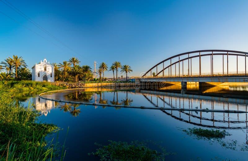 Sikt av en kyrka med en reflexion i vattnet och en bro över floden i den Alboraya regionen spain valencia arkivbild