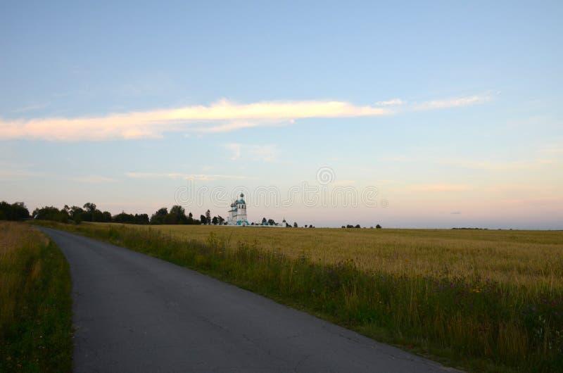 Sikt av en kyrka och en kyrkogård i avståndet bak vägen, över fältet, för solnedgång royaltyfri bild