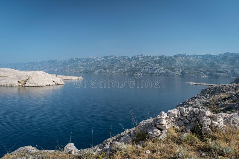 Sikt av en laguna nära ön av Pag i Kroatien med de Dalmatian bergen i bakgrunden royaltyfri bild
