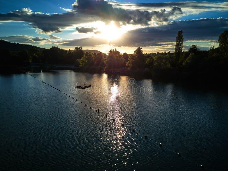 Sikt av en liten sjö och gröna träd omkring på solnedgången royaltyfri bild