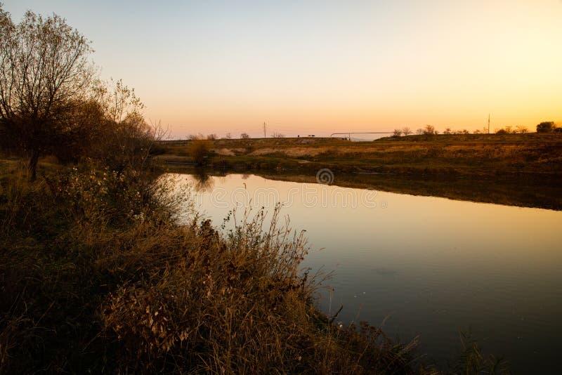 Sikt av en lugna flod med solnedgångljus arkivfoto