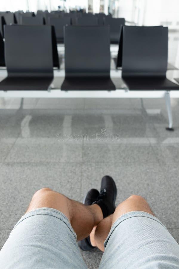 Sikt av en man& x27; s-ben som sitter i det väntande rummet på flygplatsen royaltyfria foton