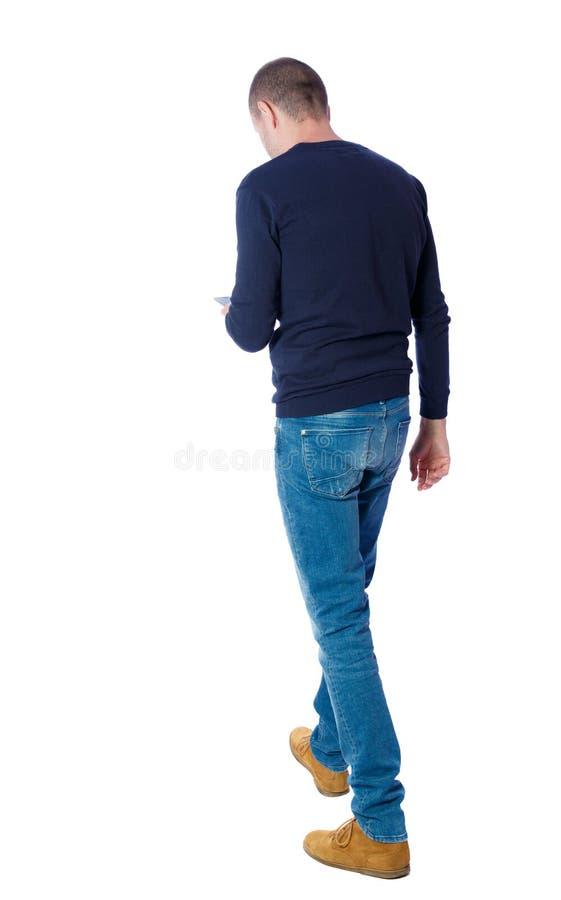 Sikt av en man som går med mobiltelefonen royaltyfri fotografi