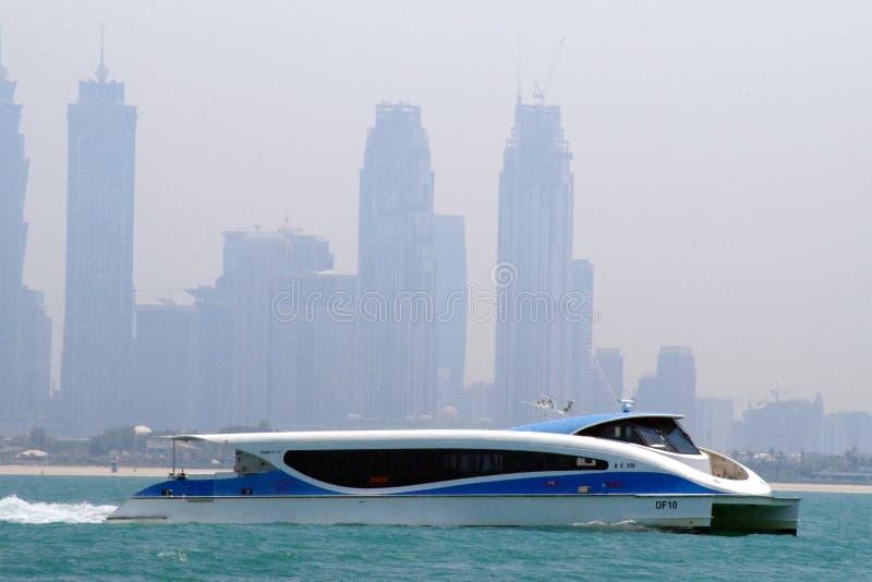 Sikt av en modern färja av offentligt trans. för Dubai vatten som förbinder flera områden inom Dubai Affärsfjärd i bakgrund royaltyfria bilder