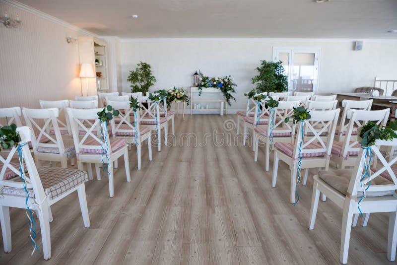 Sikt av en plats för gifta sig ceremoni i ett rum med flera rader av vita stolar och sammansättningar från olika blommor fotografering för bildbyråer