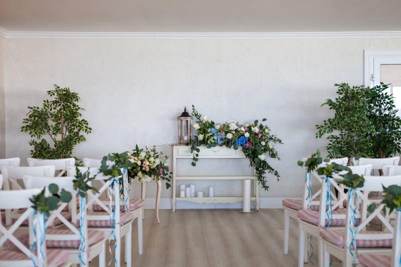 Sikt av en plats f?r gifta sig ceremoni i ett rum med flera rader av vita stolar och sammans?ttningar fr?n olika blommor arkivfoton