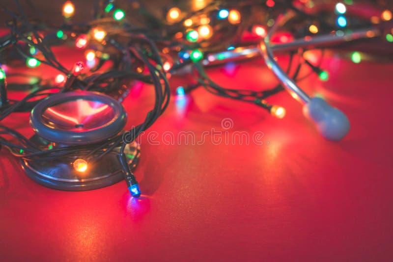 Sikt av en röd stetoskop som ligger på röd bakgrund med färgrika julljus arkivfoton