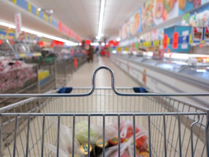 Sikt av en shoppingvagn med livsmedelsbutikobjekt royaltyfri fotografi