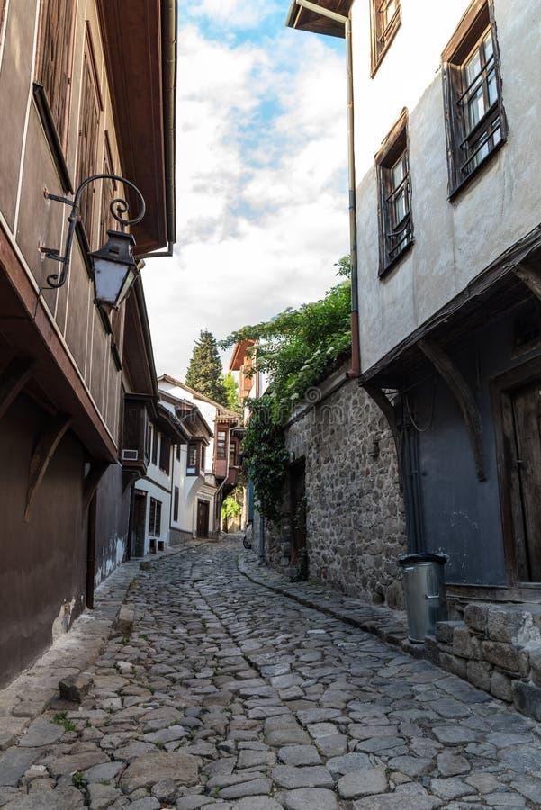 Sikt av en smal gata i historisk del av Plovdiv den gamla staden Typiska medeltida färgrika byggnader royaltyfri foto