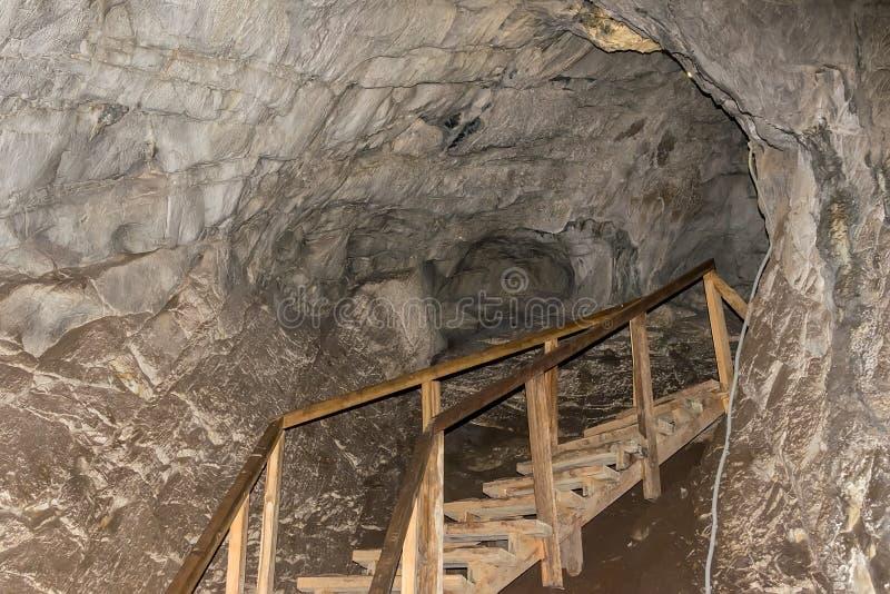Sikt av en trätrappuppgång för turister, som lokaliseras inom en stor grotta fotografering för bildbyråer