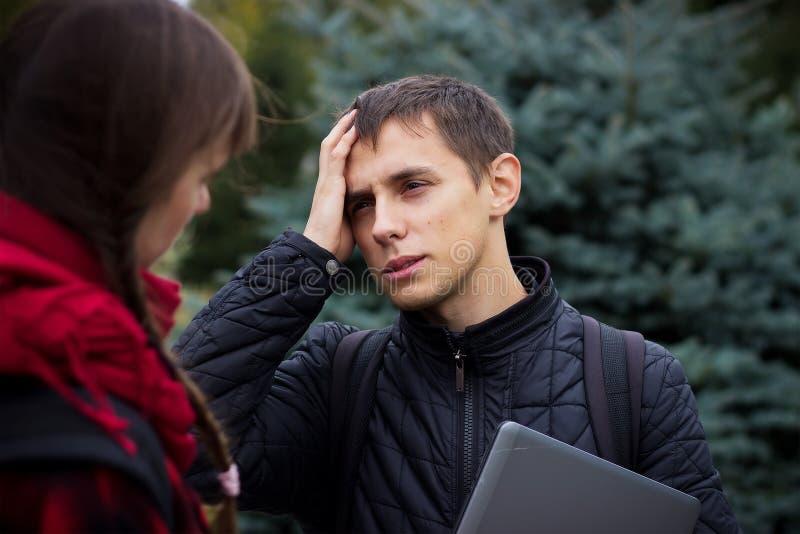Sikt av en ung studentman som har en spänning och en ångest för huvudvärk tack vare fotografering för bildbyråer