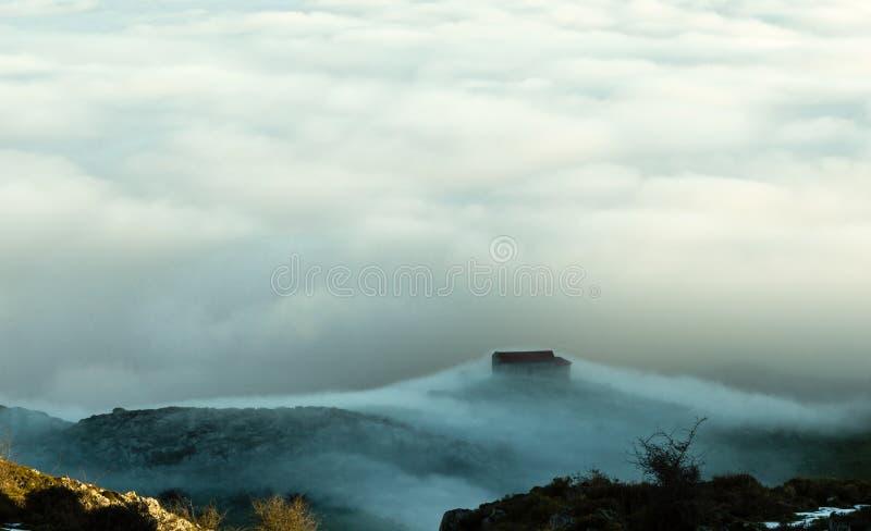 Sikt av eremitboningen av La Magdalena, på bergmonteringen Monsacro, på gryning Med moln för ett hav av bakgrund asturias spain royaltyfria bilder