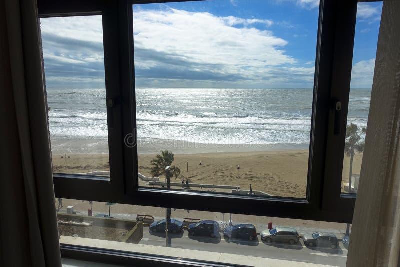 Sikt av ett hotellrumfönster av stranden och havet av Cadiz i Andalusia i Spanien royaltyfri fotografi