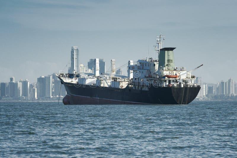 Sikt av ett stort lastfartyg som ankras och stadshorisonten på bakgrunden royaltyfri foto