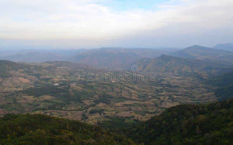 Sikt av fältet och berget - molnig sikt fotografering för bildbyråer