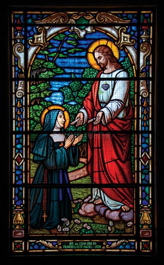 Sikt av färgrik målat glass med religiöst tema i den Bananal kyrkan arkivfoton