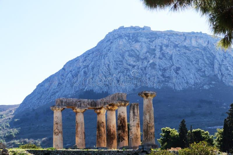 Sikt av fästningen Acrocorinth från forntida Corinth, Grekland med pelare av templet av Apollo i förgrunden royaltyfri fotografi