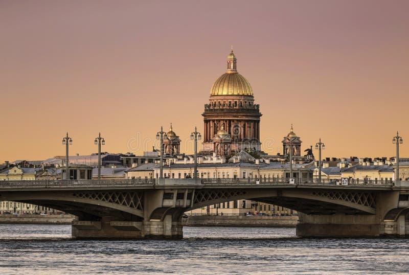 Sikt av förklaringbron över den Neva floden och kupolen av domkyrkan för ` s för St Isaac på solnedgången petersburg saint fotografering för bildbyråer