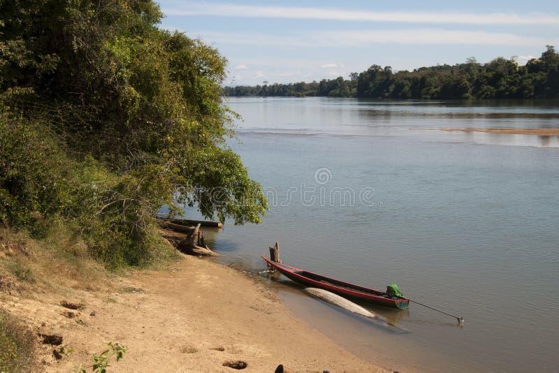 Sikt av floden med stranden och det långa fartyget i förgrund arkivfoton