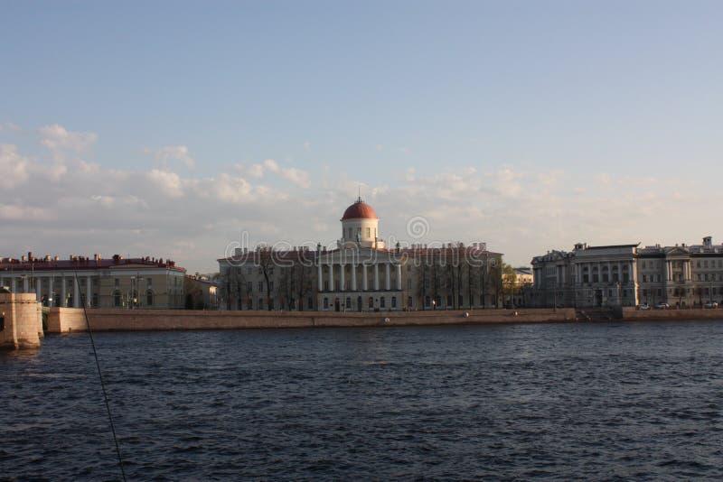 Sikt av floden och byggnaden på solnedgången royaltyfri foto