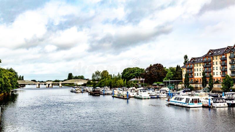 Sikt av floden Shannon med fartyg som ankras på skeppsdockan med järnvägsbron i bakgrunden royaltyfri foto