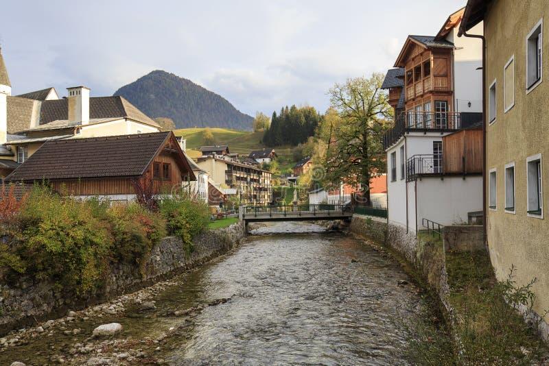 Sikt av floden som flödar till och med staden av dåliga Aussee alpin höstliggande Dåliga Aussee, Österrike arkivfoton