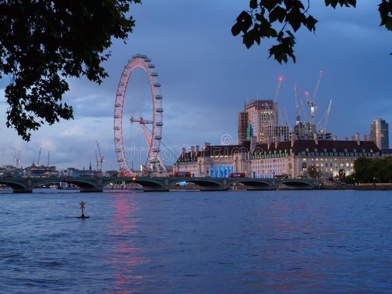 Sikt av flodThemsen med den Westminster bron, det London ögat och de arkitektoniska byggnaderna av den södra banken på natten arkivfoton