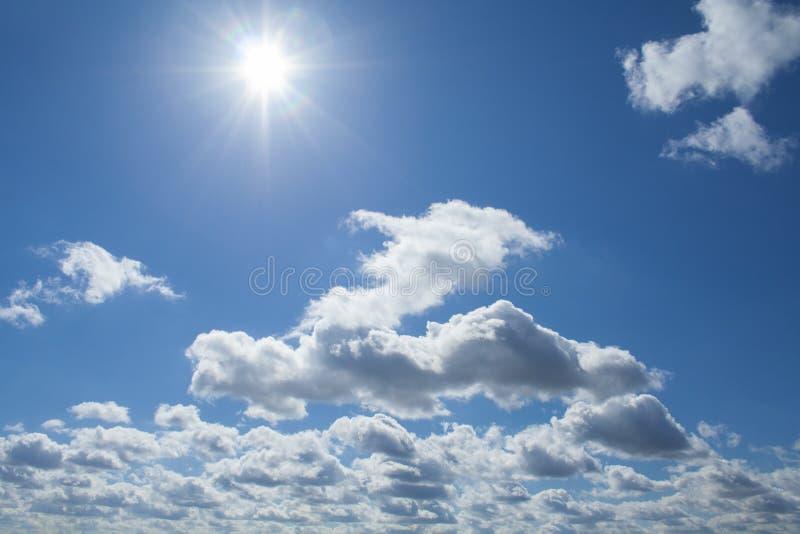 Sikt av fluffiga moln och middagsol i djupblå himmel royaltyfri fotografi