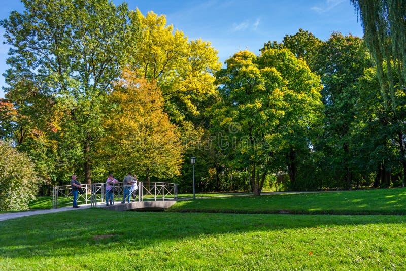 Sikt av folk som tycker om en härlig solig dag i den engelska trädgården i Munich, Tyskland royaltyfri bild