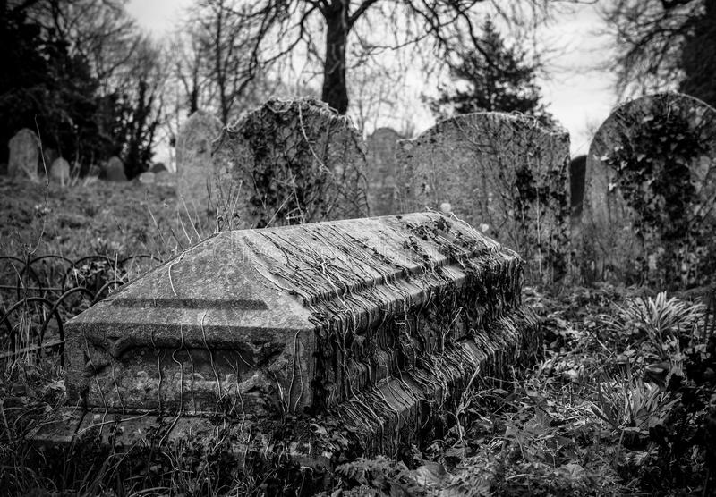 Sikt av gamla gravstenar som ses i monokrom, i en lika gammal kyrkogård arkivfoton